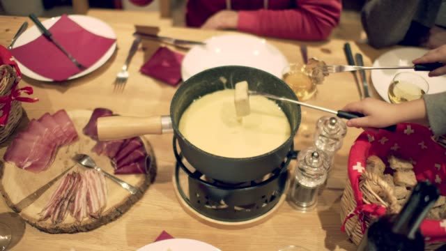 Fondue Family enjoy Swiss Fondue Cheese at the Dinner by the Table chalet stock videos & royalty-free footage