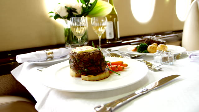 Food and drink served on a table 4k Food and drink served on a table in private jet 4k military private stock videos & royalty-free footage