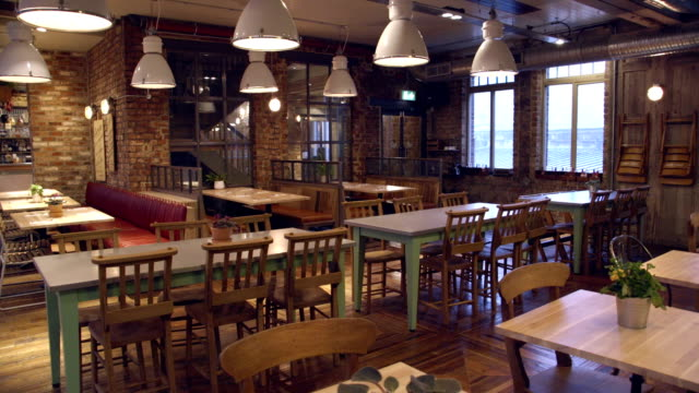 Food and Drinks Establishment with a Traditional Modern Twist Interior of a traditional British food and drinks establishment with a modern twist. No people. Table, chairs, stools and bar counter seen with overhead lighting. bar counter stock videos & royalty-free footage