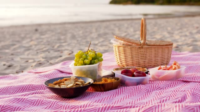 food and picnic basket on blanket on beach leisure and concept - food and picnic basket on blanket on beach snack stock videos & royalty-free footage