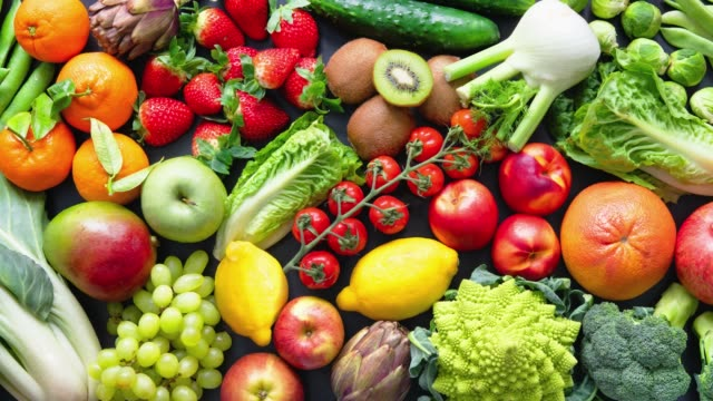 vídeos de stock, filmes e b-roll de fundo alimentar com variedade de frutas e vegetais orgânicos frescos - fruta