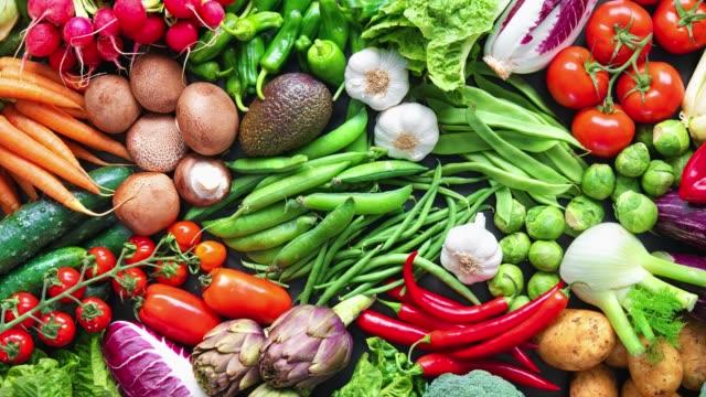 matbakgrund med sortiment av färska ekologiska grönsaker - hälsosamt ätande bildbanksvideor och videomaterial från bakom kulisserna