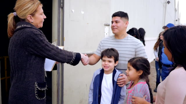 Food bank volunteer greeting Hispanic family while in line for donations Food bank volunteer greeting Hispanic family while in line for donations poverty stock videos & royalty-free footage