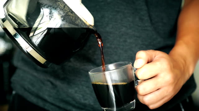 Food Cinemagraphs: A man pouring a mug of hot coffee from a glass pot in the morning at home.