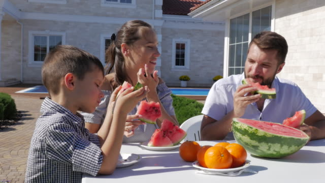 food cinemagraphs. young happy family eating watermelon at the cottage - picnic video stock e b–roll