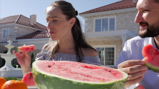 Food Cinemagraphs. young happy family eating watermelon at the cottage Mom, dad and son eat fruit in front of the country house. three persons. watermelon stock videos & royalty-free footage