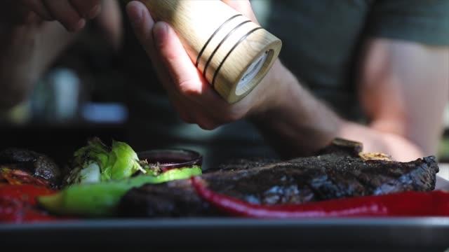 vídeos de stock e filmes b-roll de food closeup. man hand seasoning steak meat with grounded pepper - meat plate