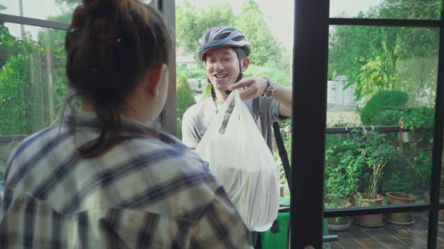 vídeos de stock e filmes b-roll de food courier deliver order to the customer home and taking payment - entregar