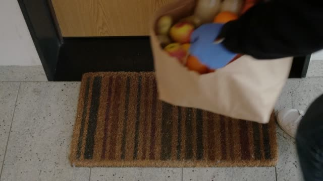 food delivery courier gloves leaving grocery bag in front door
