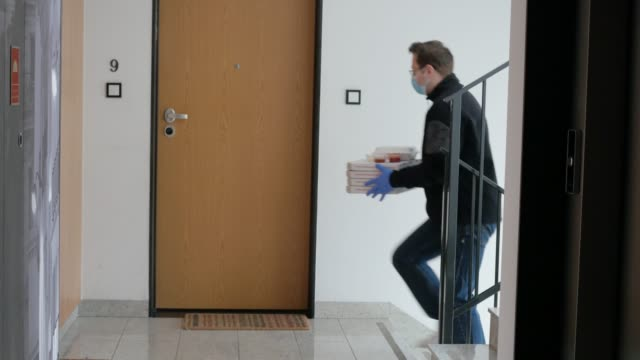 food delivery courier protective mask leaving boxes with pizza in front door
