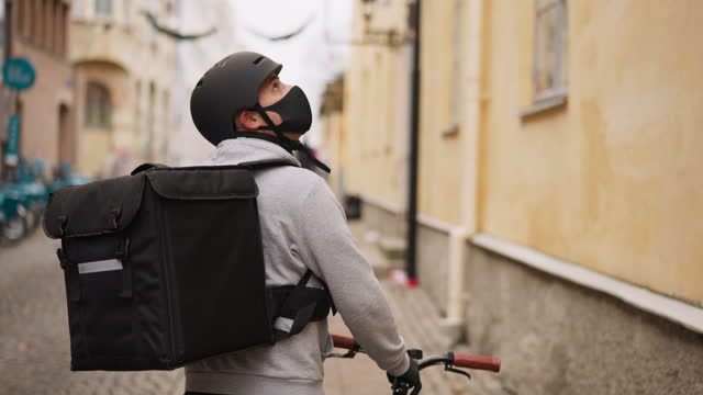 Food delivery man looking for the right address Male bike delivery person, wearing a face mask. He is using his smart phone to find the right address. behind stock videos & royalty-free footage