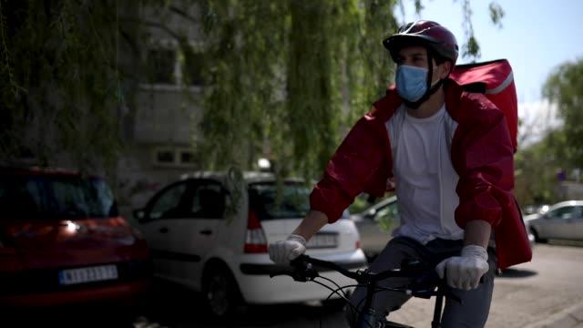 vidéos et rushes de livreur de nourriture sur ses tours de livraison avec son vélo - livre