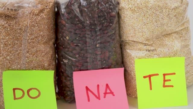vídeos y material grabado en eventos de stock de donaciones de alimentos en una bolsa de papel sobre un fondo blanco. entrega de alimentos - food drive