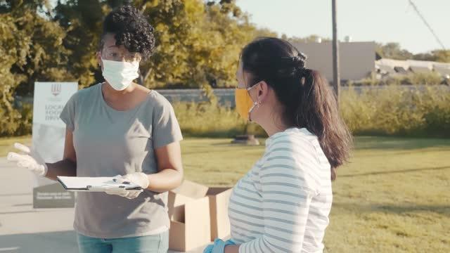 vídeos y material grabado en eventos de stock de coordinadora de food drive discute tareas con una voluntaria femenina - food drive