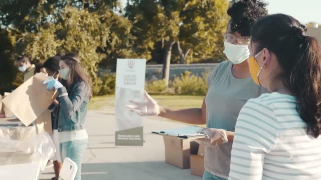 vídeos y material grabado en eventos de stock de voluntario de food drive obtiene orientación voluntaria del coordinador de alimentos - food drive