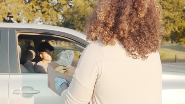 Food drive volunteer gives box of food to woman A mid adult female food drive volunteer carries a box of food to a woman waiting in a car. The woman smiles and thanks the volunteer for the food. The volunteer waves as she walks away. giving tuesday stock videos & royalty-free footage