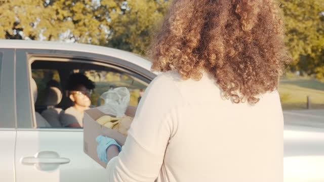 gıda sürücü gönüllü kadına yiyecek kutusu verir - giving tuesday stok videoları ve detay görüntü çekimi