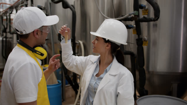 Food engineer talking to an operator at a beer factory and looking at a sample Food engineer talking to an operator at a beer factory and looking at a sample - industrial concepts quality control stock videos & royalty-free footage