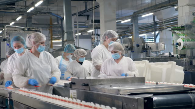 Food factory equipment with women relocating packaged food. video
