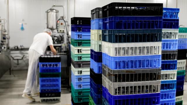 Food factory.The worker packs plastic glasses of yogurt Food factory.The worker packs plastic glasses of yogurt crate stock videos & royalty-free footage
