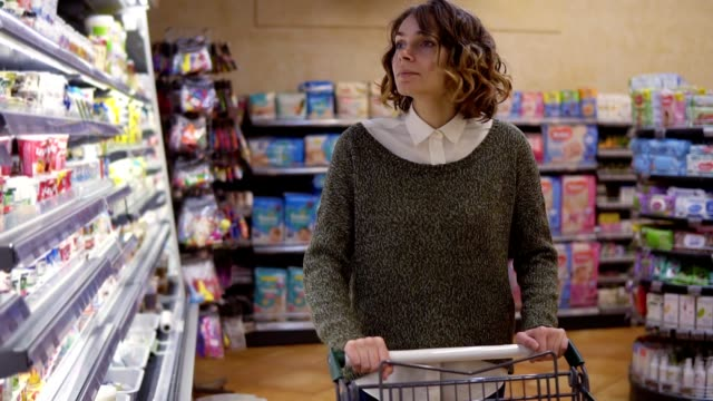 Food, Health Concept - Woman in a supermarket standing in front of the freezer shelfs and choose buying a bottle of jogurt, taking one and put it to the cart . Slow motion video