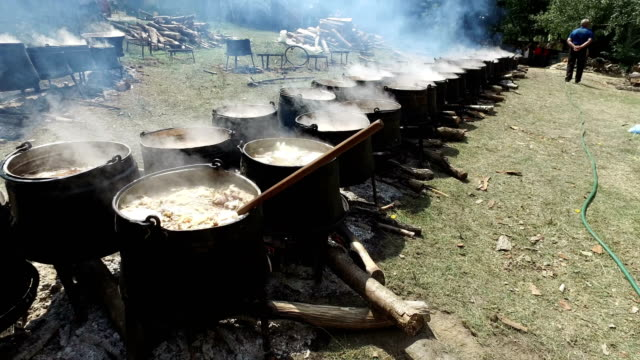 Food in a cauldron on a fire. Cooking outdoors in cast-iron cauldron video