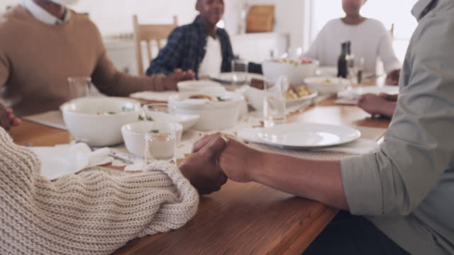 Food is what you need to get the family together 4k video footage of a multigenerational family saying grace before a meal black people stock videos & royalty-free footage