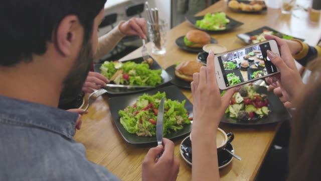 essen fotos. schließen sie die hände von frauen, die fotos machen im restaurant - salat speisen stock-videos und b-roll-filmmaterial