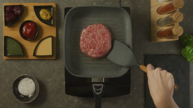 Food preparation Overhead view of a kitchen counter and human hands while turning over the hamburger in the pan. There are sauces, spices and salt on the table. ground beef stock videos & royalty-free footage