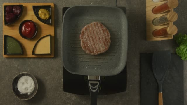 Food preparation Overhead view of a kitchen counter and human hands while adding salt over hamburger in the pan. There are sauces, spices and salt on the table. ground beef stock videos & royalty-free footage