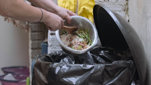 Food remains are dumped in the bin Woman throwing away leftovers from dinner leftovers stock videos & royalty-free footage