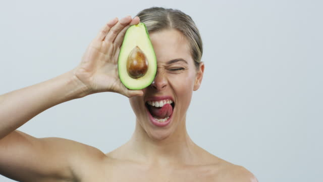 Food that nourishes the skin and the body 4k video footage of an attractive young woman holding an avocado in front of her face against a grey background avocado stock videos & royalty-free footage