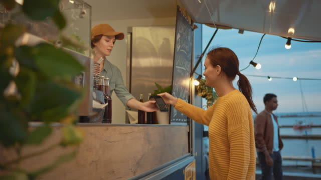 food truck employee hands out a freshly made burger to a happy young female. young lady is paying for food with contactless credit card. street food truck selling burgers in a modern hip neighbourhood - credit card filmów i materiałów b-roll