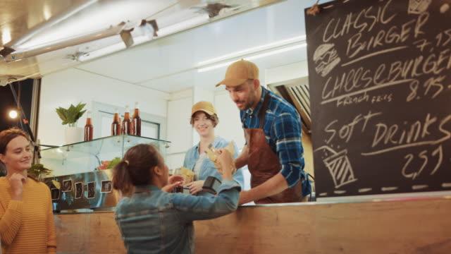 vidéos et rushes de l'employé de camion de nourriture distribue un hamburger fraîchement fait à une jeune femelle heureuse. jeune dame paie pour la nourriture avec la carte de crédit sans contact. camion de nourriture de rue vendant des hamburgers dans un voisinage modern - lieu sportif