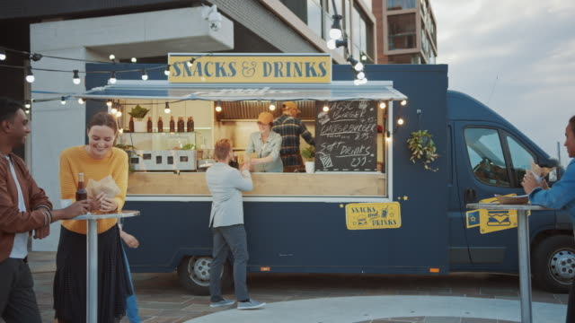 food truck employee hands out a freshly made gourmet burger to a happy young man in a suit. female employee smiles and looks at the camera. street food truck selling burgers in a modern neighbourhood. - furgone video stock e b–roll