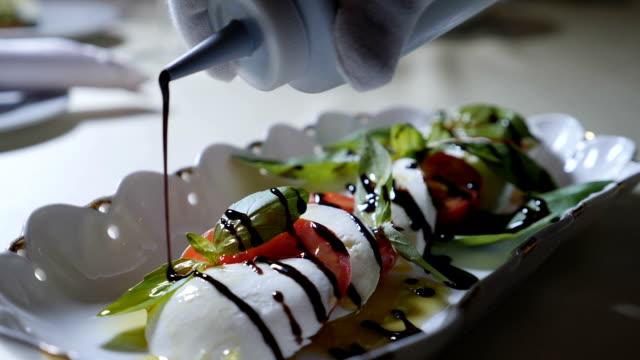 food video. healthy food and vegetarian concept. close up of pouring vinegar over caprese salad. italian caprese salad with mozzarella cheese. slow motion - готовый к употреблению стоковые видео и кадры b-roll