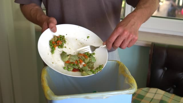 Food Waste. Throwing away meal Food Waste. A man throws the uneaten food from a plate in the trash bin. Throwing away meal leftovers stock videos & royalty-free footage