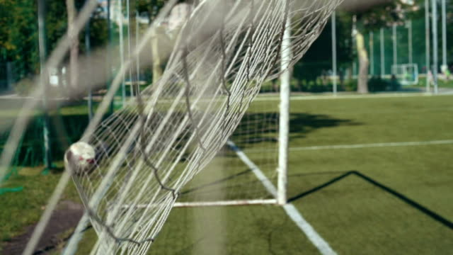 Foot ball getting into  football goal, slow motion