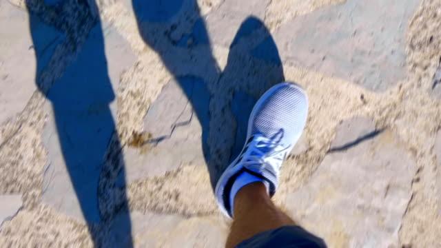 vidéos et rushes de pied en baskets blanches commencent à marcher le long de la route faite de pierres - homme slip