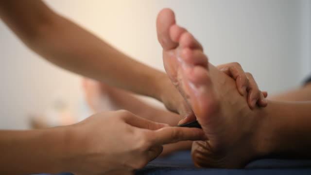 stockvideo's en b-roll-footage met voet massage in de spa salon. - massagetherapeut