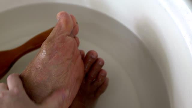 foot massage,hand massaging feet with sea salt - pedicure filmów i materiałów b-roll