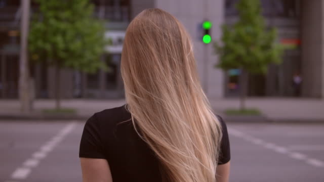 foot passenger crosses the road back view woman wearing black dress with long blond hair walking on pedestrian crossing. city landscape and green traffic light. successful businesswoman going to the office building human back stock videos & royalty-free footage