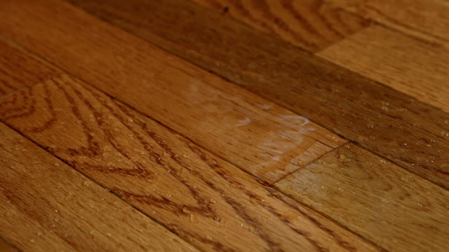 A foot slips on water dripping from above on a wood floor