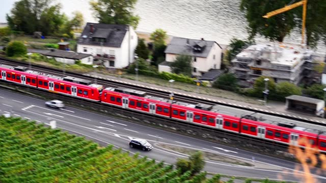 Footage, a red passenger train goes through the city.