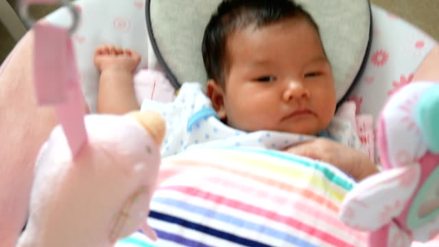vídeos de stock, filmes e b-roll de filmagens de 4k, adorável bebê asiático sente sono, deitado em um berço de balanço - mobile