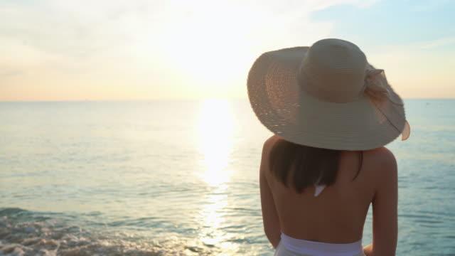 vidéos et rushes de vidéo 4k fille touriste asiatique sur la plage. elle porte un maillot de bain le matin. - chapeau