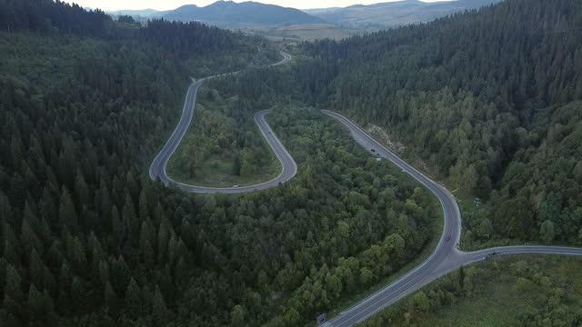 materiał b rolki aerial view drone latające nad krajobraz serpentine krętej drogi. samochodem jadącym krętą drogą. drone 4k wideo. w góry w letni słoneczny dzień. okrężną - mountain top filmów i materiałów b-roll