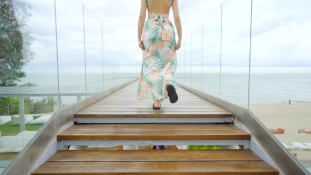 4K footage Beautiful woman walking on the glass stairs