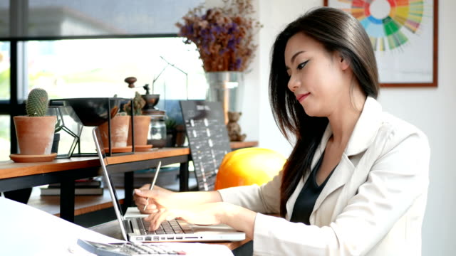 4K footage, busy business woman working with laptop computer and thinking with serious face in coffee shop cafe in the city in the morning , business people lifestyle. Asian model in her 30s video