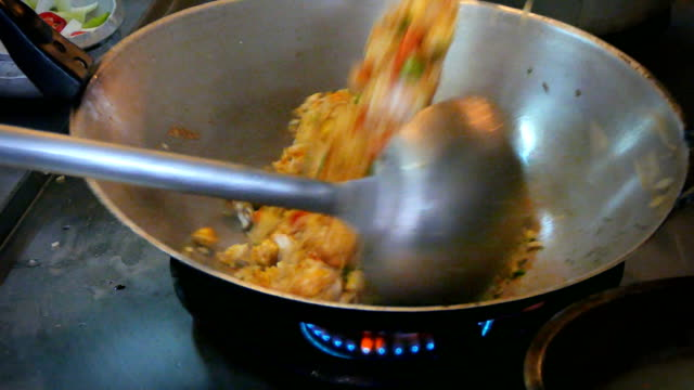 4k footage, close up chef hand cooking thai style fried rice in old frying pan. - smażony filmów i materiałów b-roll